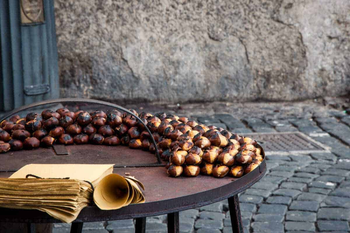 Roasted Chestnut stand with paper cones - One of the things to do in Europe in winter is experience the chestnut festival in Portugal