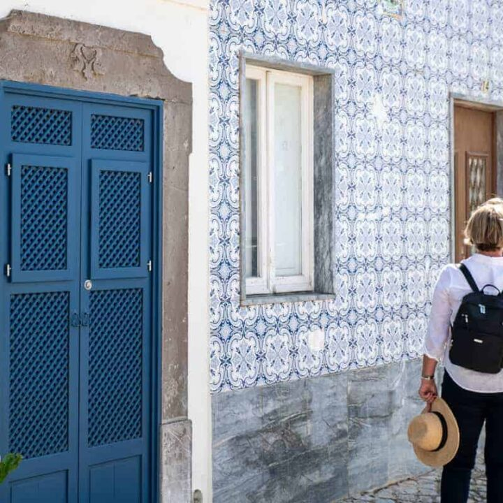 Lady standing in a quaint cobblestone street in Portugal looking at the tiled houses, holding a sunhat wearing a small anti-theft backpack