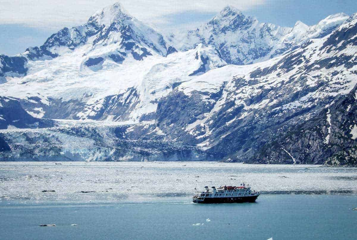 Alaskan winter cruise ship looking small against the ice and mountains.