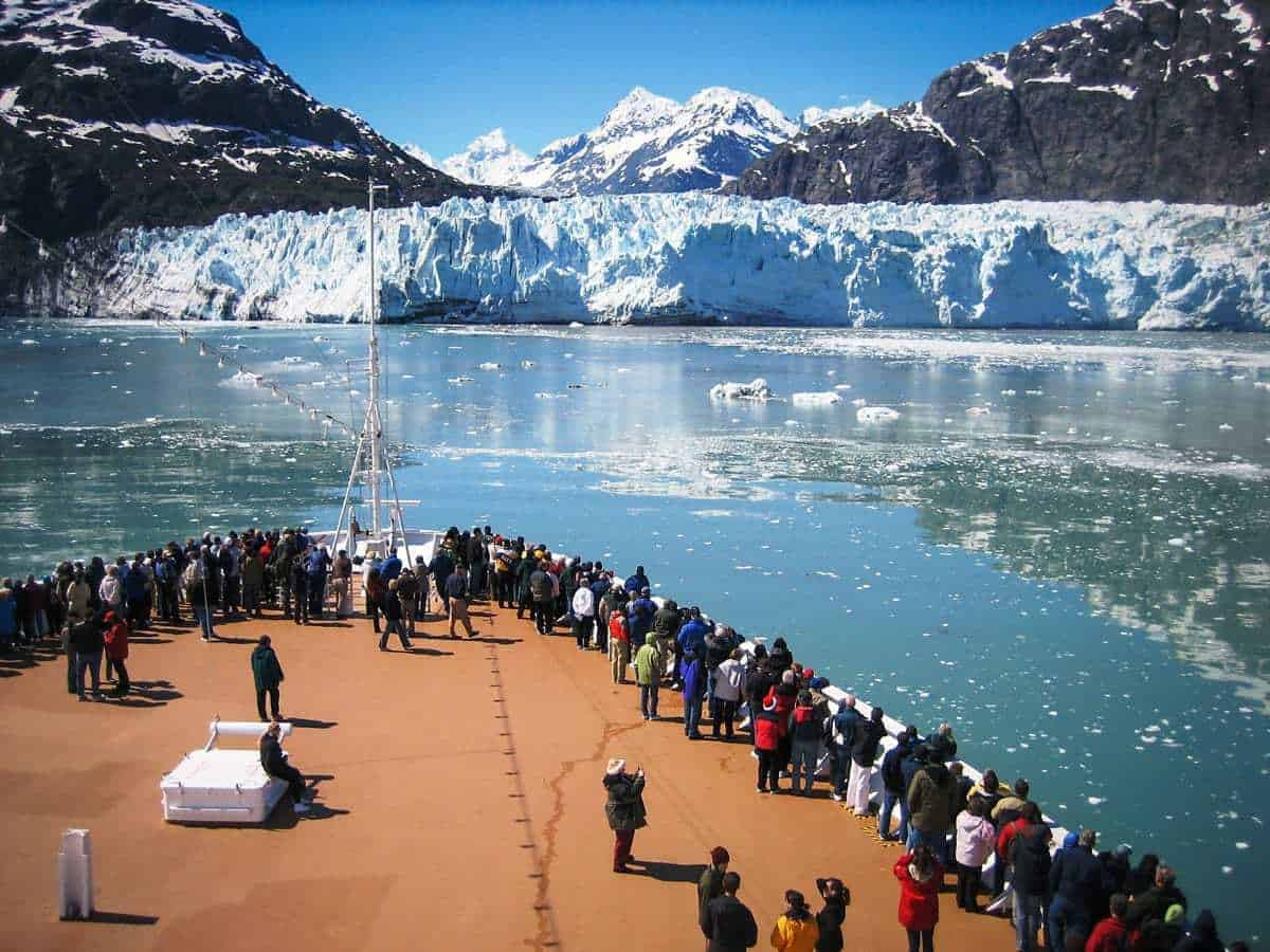 Tourists on the bow of a ship looking at Alaskan glaciers.