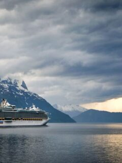 Cruise ship steaming through a wintery fjord with snow capped mountains in the background. These are some of the best winter cruises.