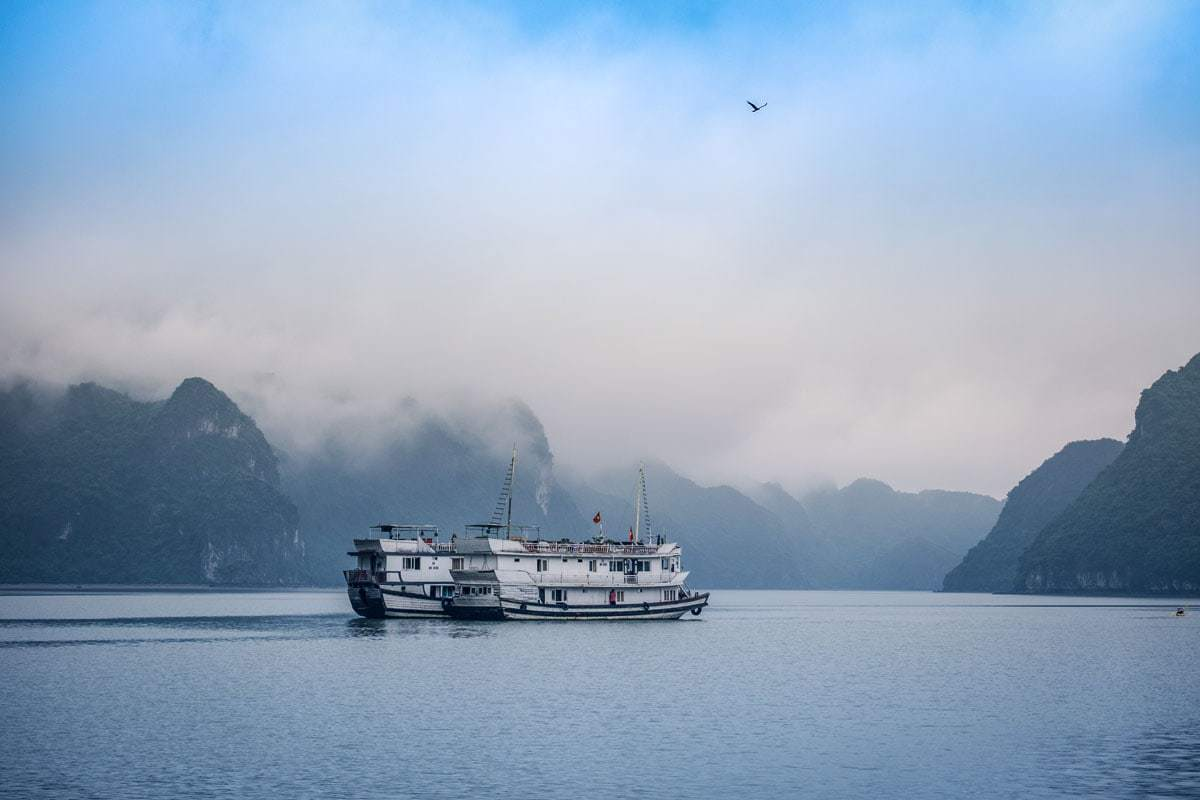 Winter cruise ship in Halong bay with beautiful fog drenched landscape.