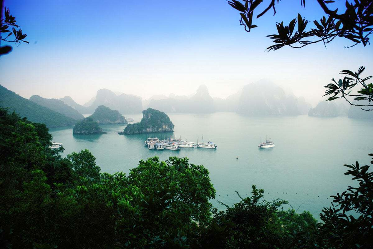 Mist falls over Halong Bay in winter creating a mysterious landscape with boats anchored in Halong Bay.