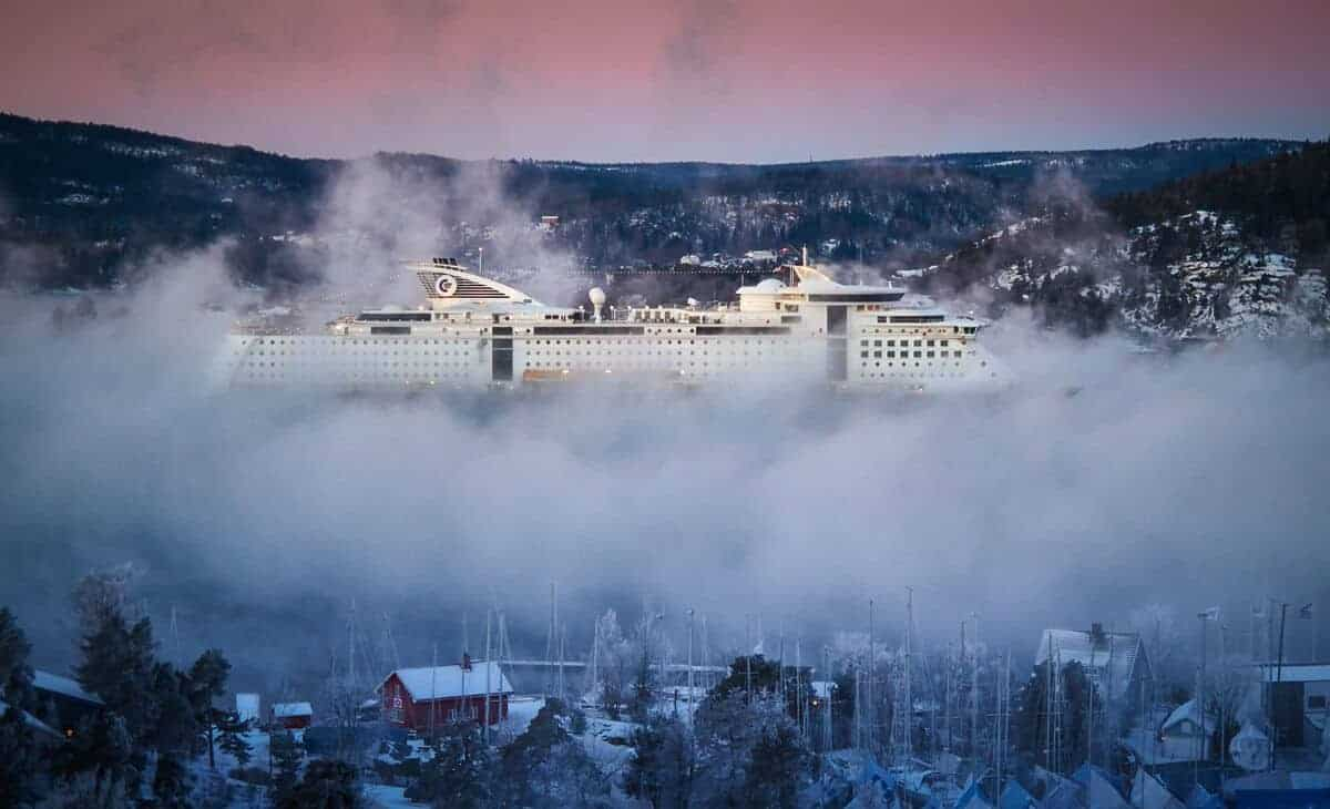 A cruise ship moves though Norwegian towns in a mist of snow.