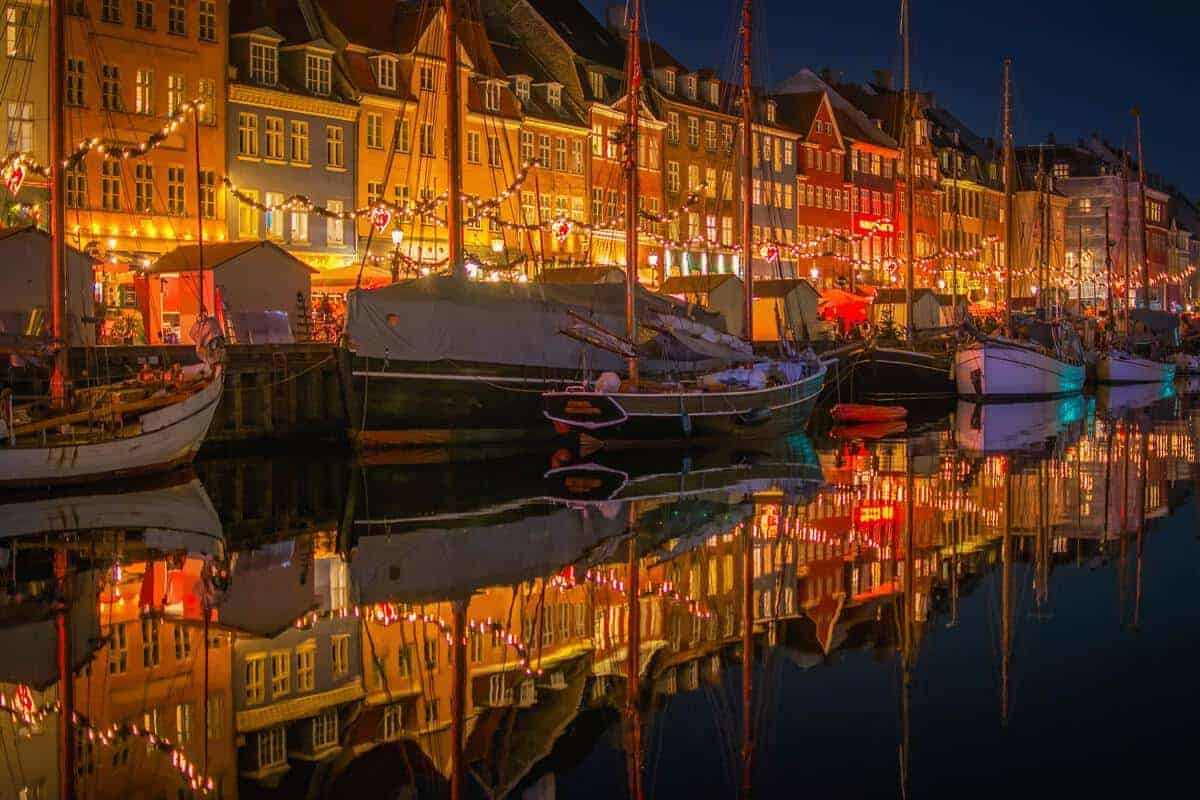 Copenhagen waterfront at Christmas time with yachts decorated in lights.