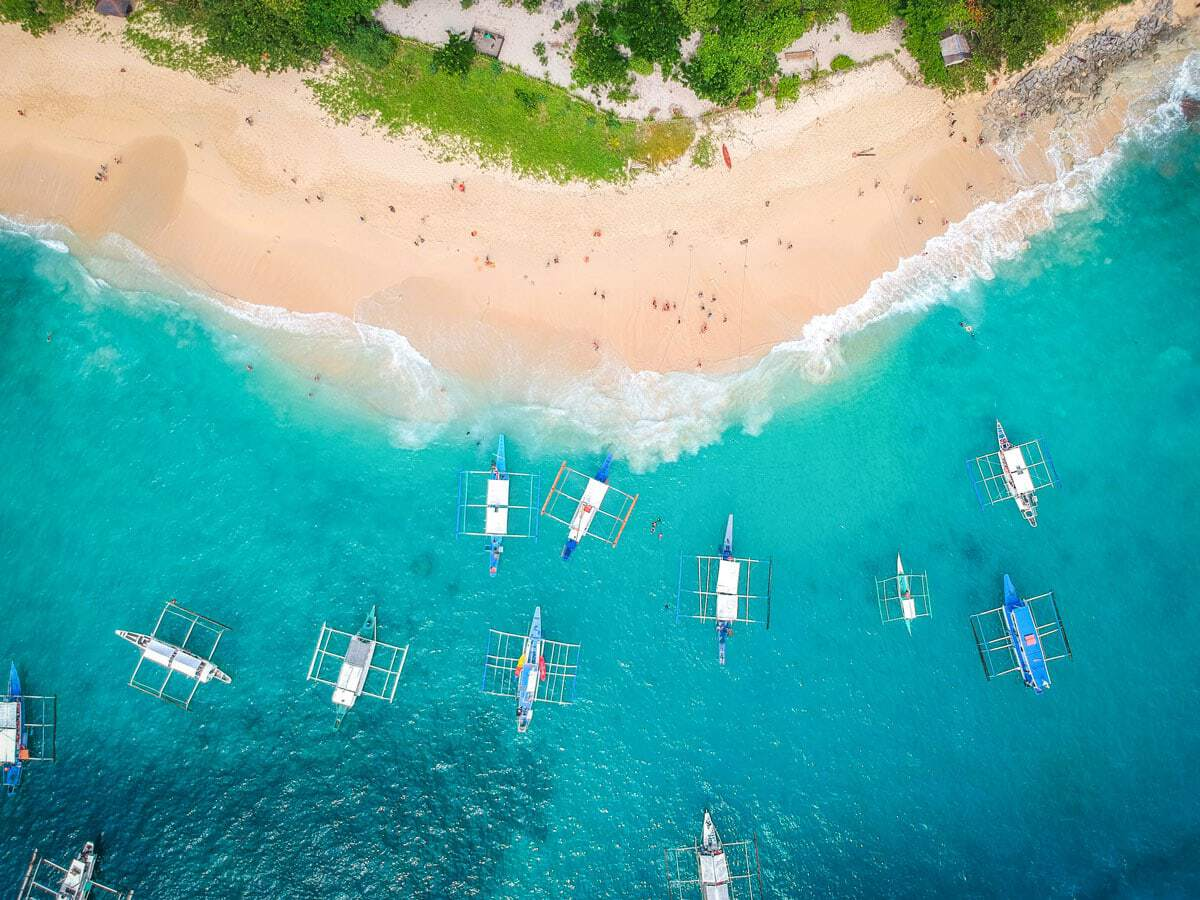 An aerial view of boats anchored in clear water off a white sand beach. Just one of the idyllic scenes from the best places to visit in Southeast Asia