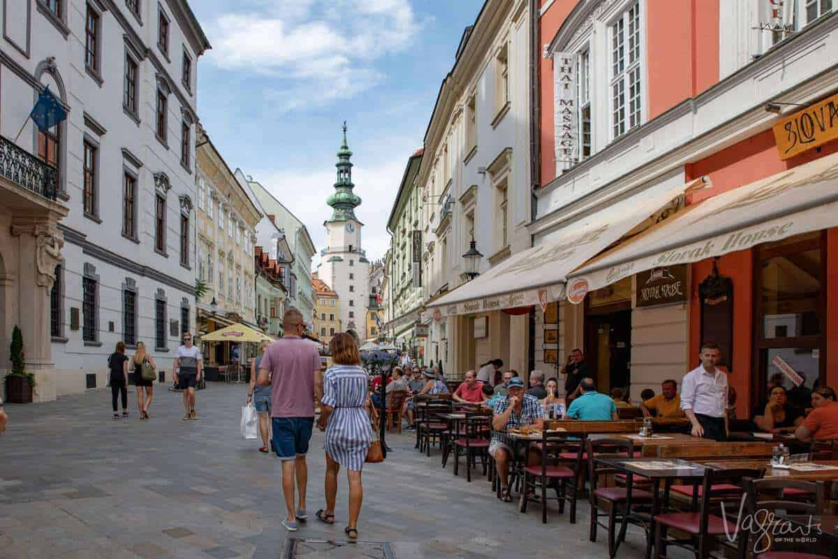 People walking down a shopping esplanade with a church steeple in the background and diners eating alfresco along the way. You may ask what should I pack for a european river cruise. The cruise packing tips here is to always be prepared for changes in the weather. You never know when it may be sunny and warm even in winter.