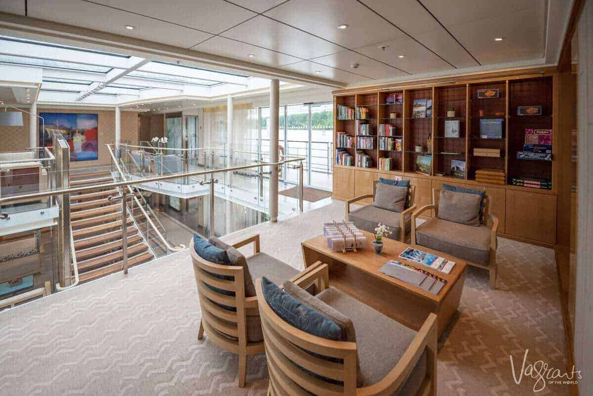 Reading and games area on a viking river cruise with shelves of books and a view of the ships atrium in the background. How should you dress for a viking cruise. Smart casual is the answer, remember you are on holiday and want to look good and be comfortable.