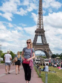 Young girl standing in front of the Eiffel Tower in Paris wearing a crossbody handbag. This is the best type of anti theft purse for travel