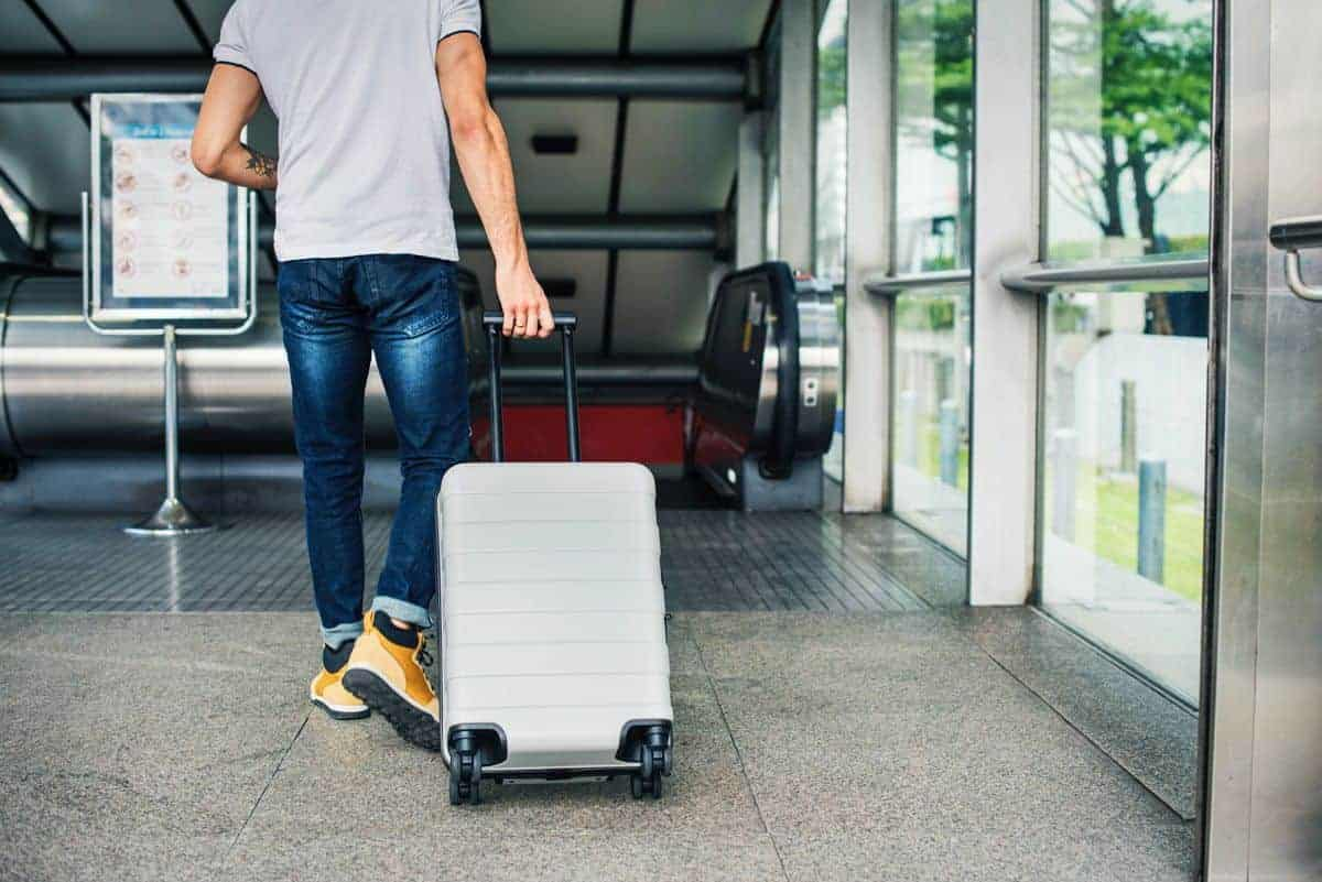 Man pulling suitcase through an airport. Make sure you have the best travel locks for all your luggage when you travel.