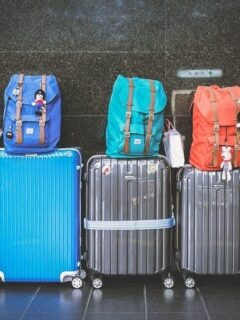 Suitcases and backpacks lined up against a wall. A Guide to Buying The Best Travel Luggage Locks