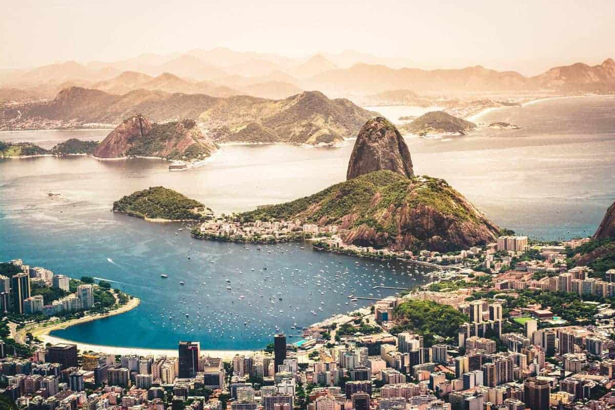 small bay with mountain background and city in the forefront. when is the best time to visit brazil, anytime as long as you go, there are so many great things to see and do that should be included in your brazil itinerary