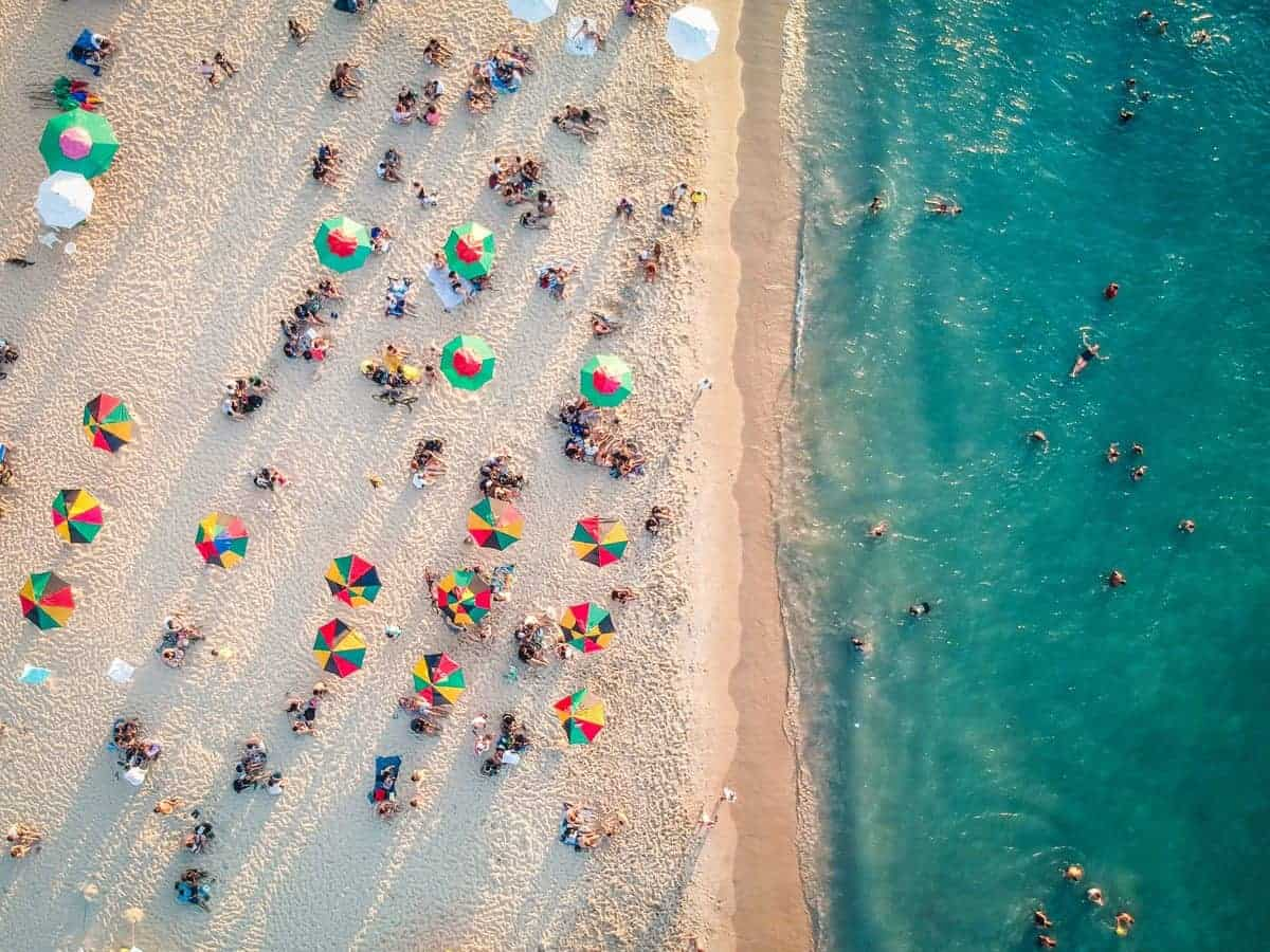 Beach and blue ocean with colourful umbrellas and beach goers.