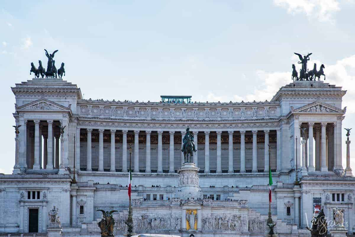 Piazza Venezia with man on horse statue at the front and chariots either side.