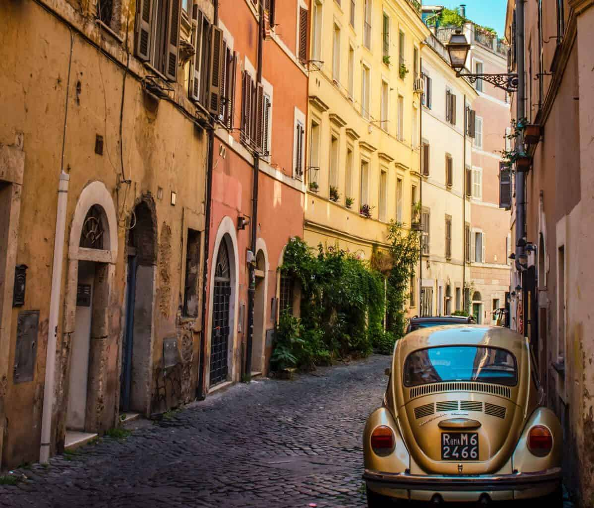 A VW car parked in colourful street in Trastevere neighbourhood.