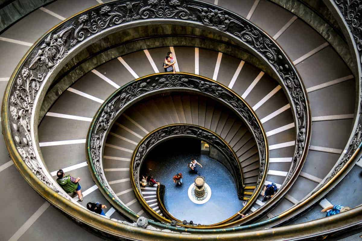 Mother hugging son on spiral staircase inside Vatican Museum.
