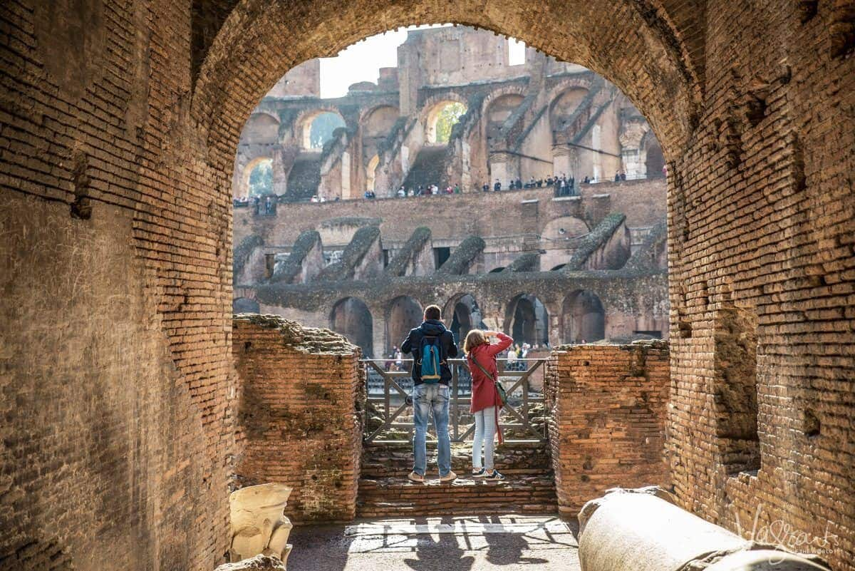 A man and women looking out over The Colosseum. How much does it cost to visit the Roman Colosseum? Read on we cover all you need to know about visiting Rome.