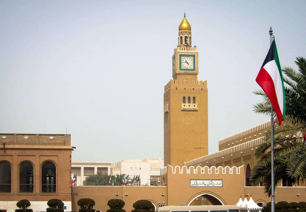 Clock tower and Kuwait flag flying.