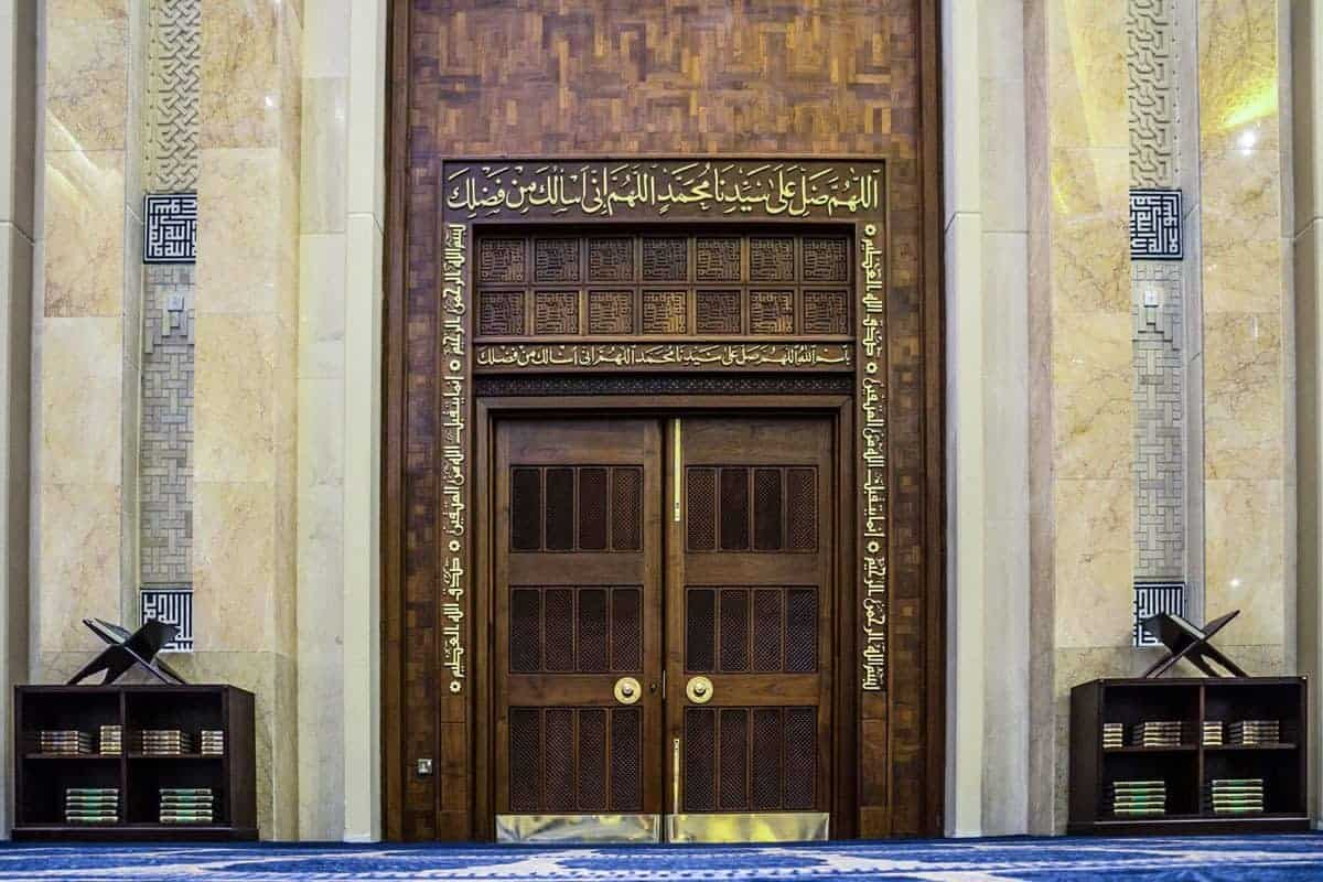 Wooden parquet doors with gold lettering at the grand mosque.