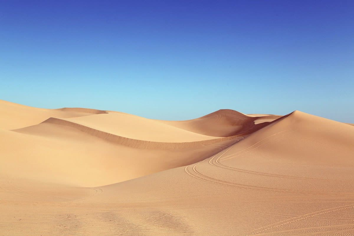Desert sand dunes against a blue sky.