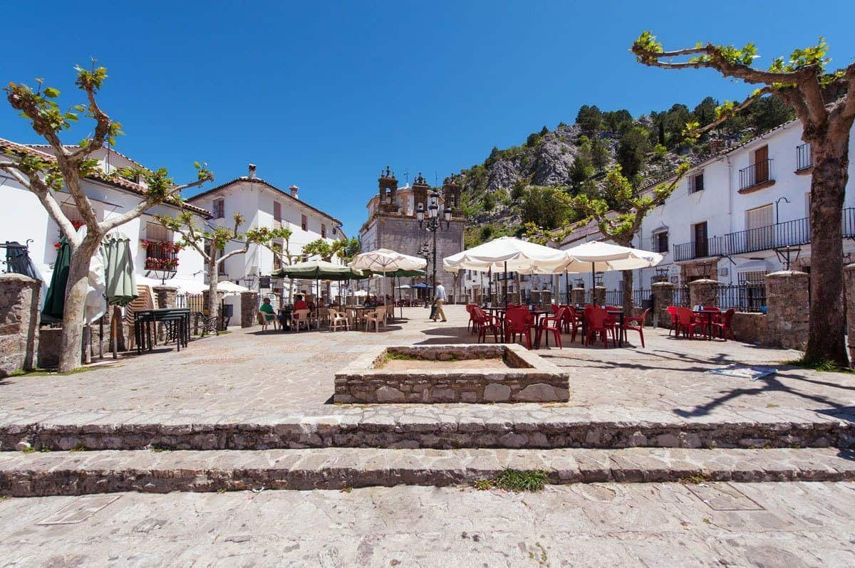 Outdoor restaurants in the village square of Grazalema Spain one of the Pueblos Blancos villages and great place to stop for lunch on your southern spain itinerary