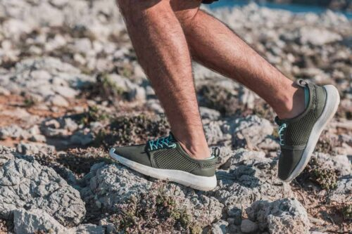 Closeup of mans legs walking on rocks wearing Tropicfeel sneakers, the best travel shoes for all occasions.