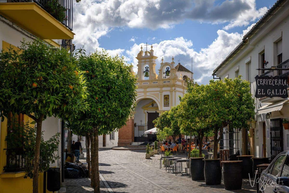 Orange tree lined street with yellow church and bell tower in Zahara de la Sierra Spain.
