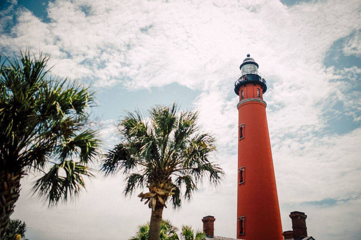 red lighthouse and palm trees in key west. best place for diving and snorkelling in usa this summer