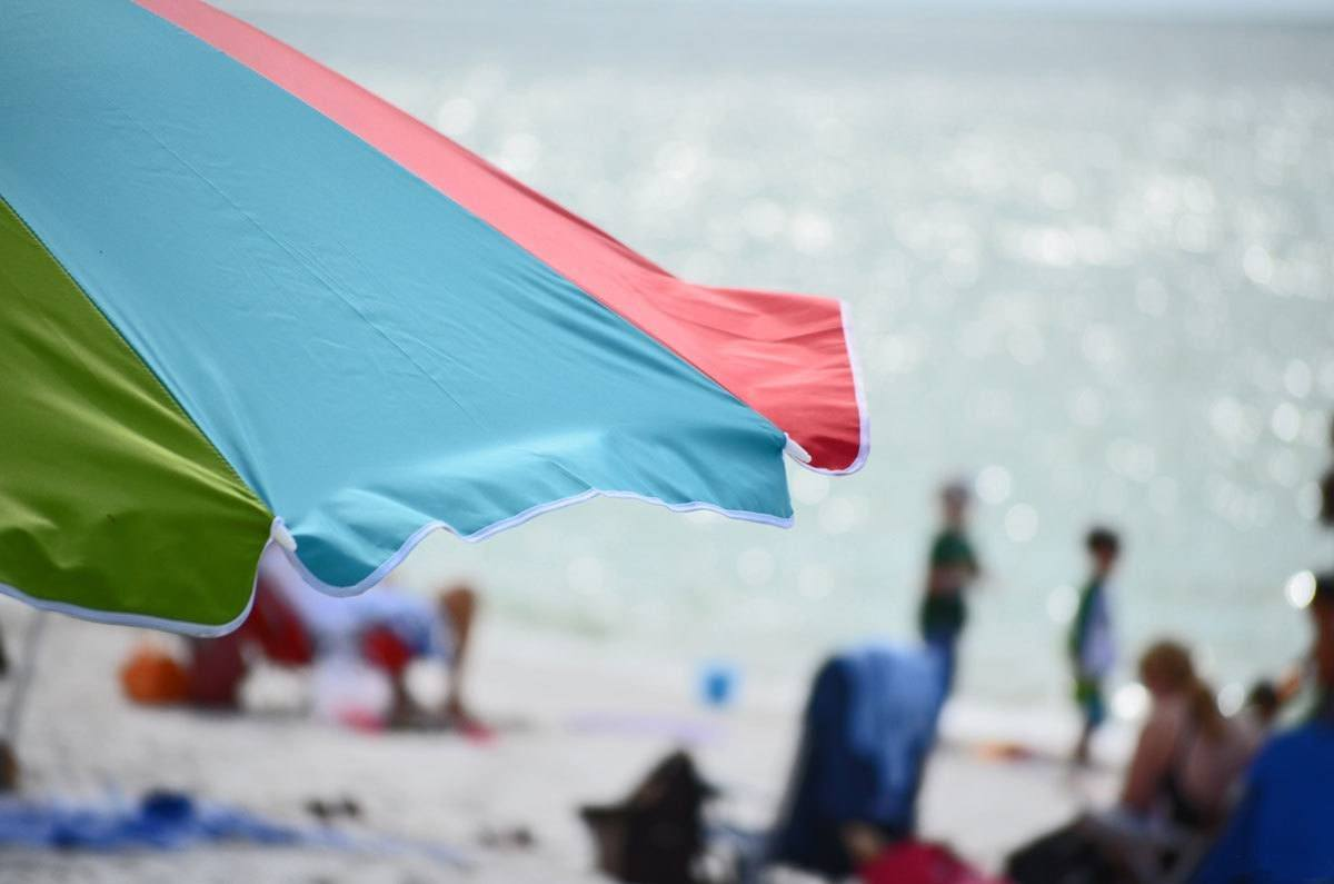 Beach umbrella with out of focus beach, summer is the best time to visit florida