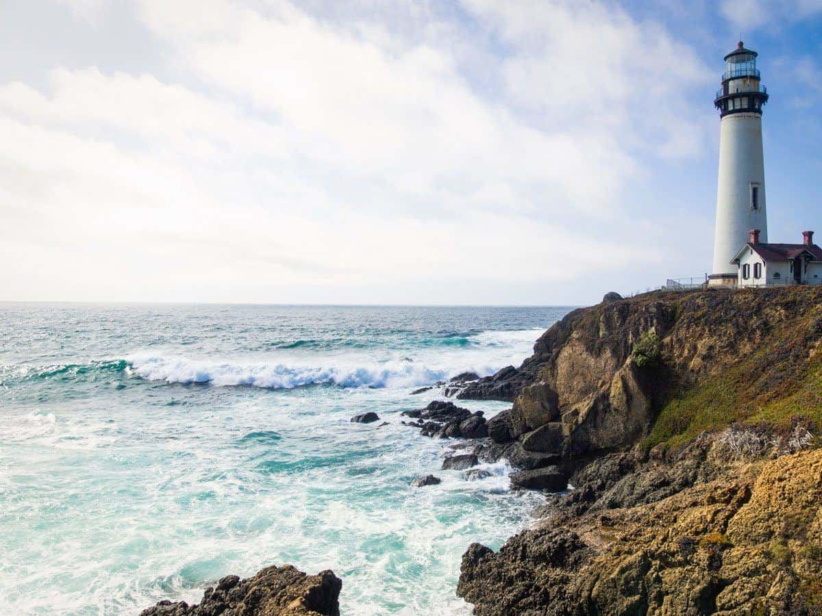 waves crashing against point with lighthouse in California the most popular summer destination in usa