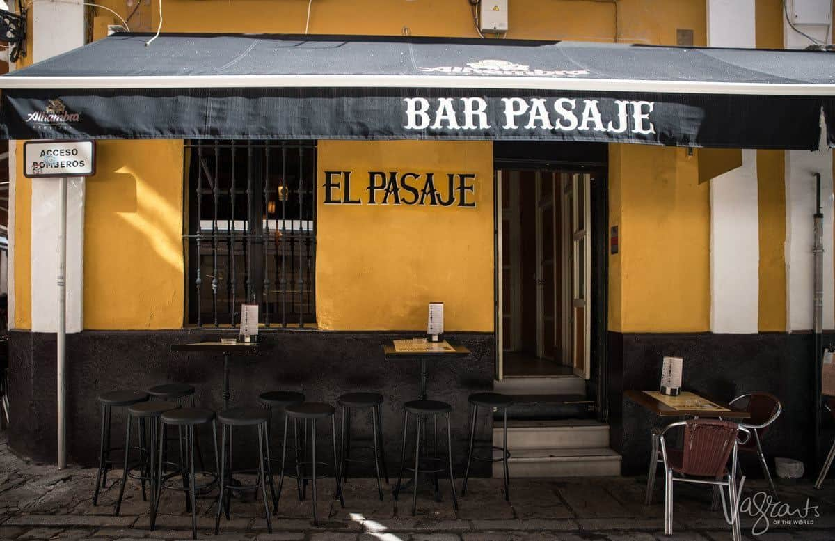 Orange and black sign of El Pasaje a popular place to drink in seville