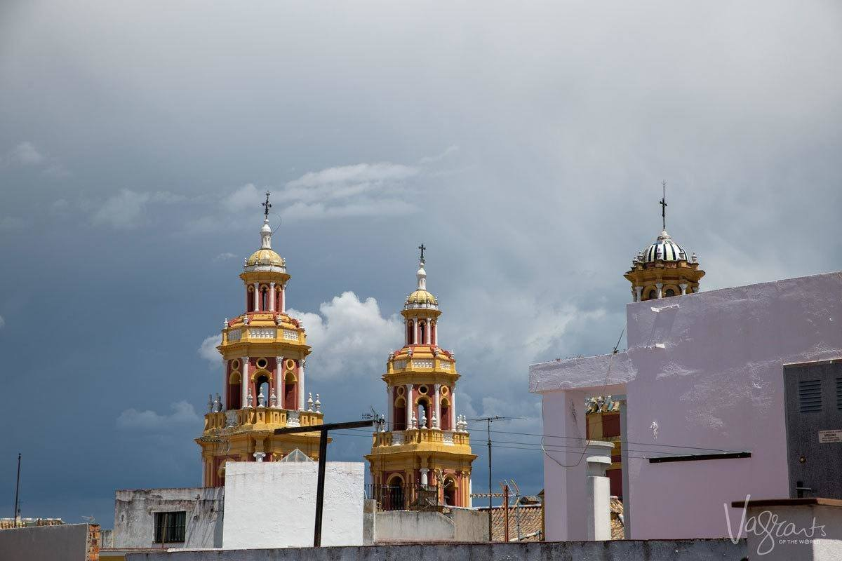a stormy sky behind the golden bell towers of the catheral. There is plenty to see and do in Seville on your own.