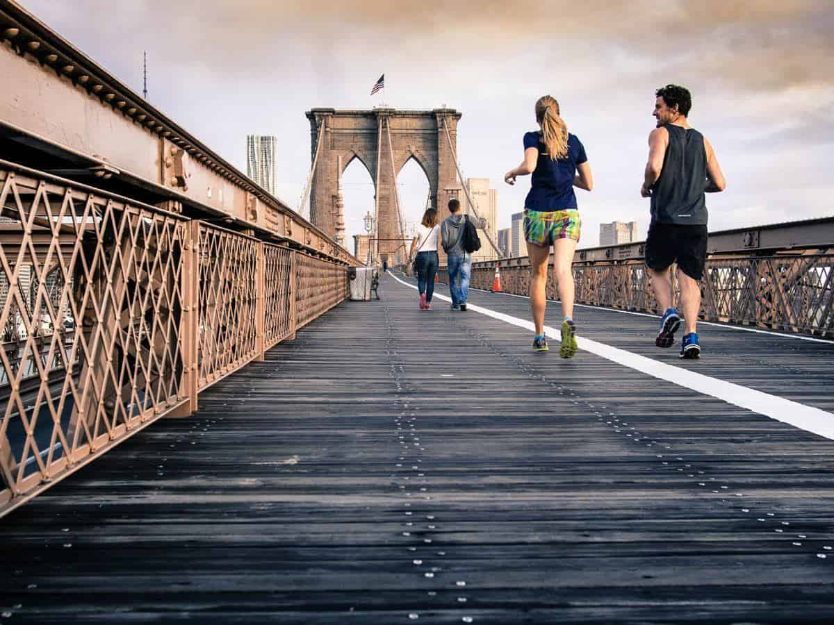 Jogging is a great travel workout routine. A couple joging across a bridge in the city