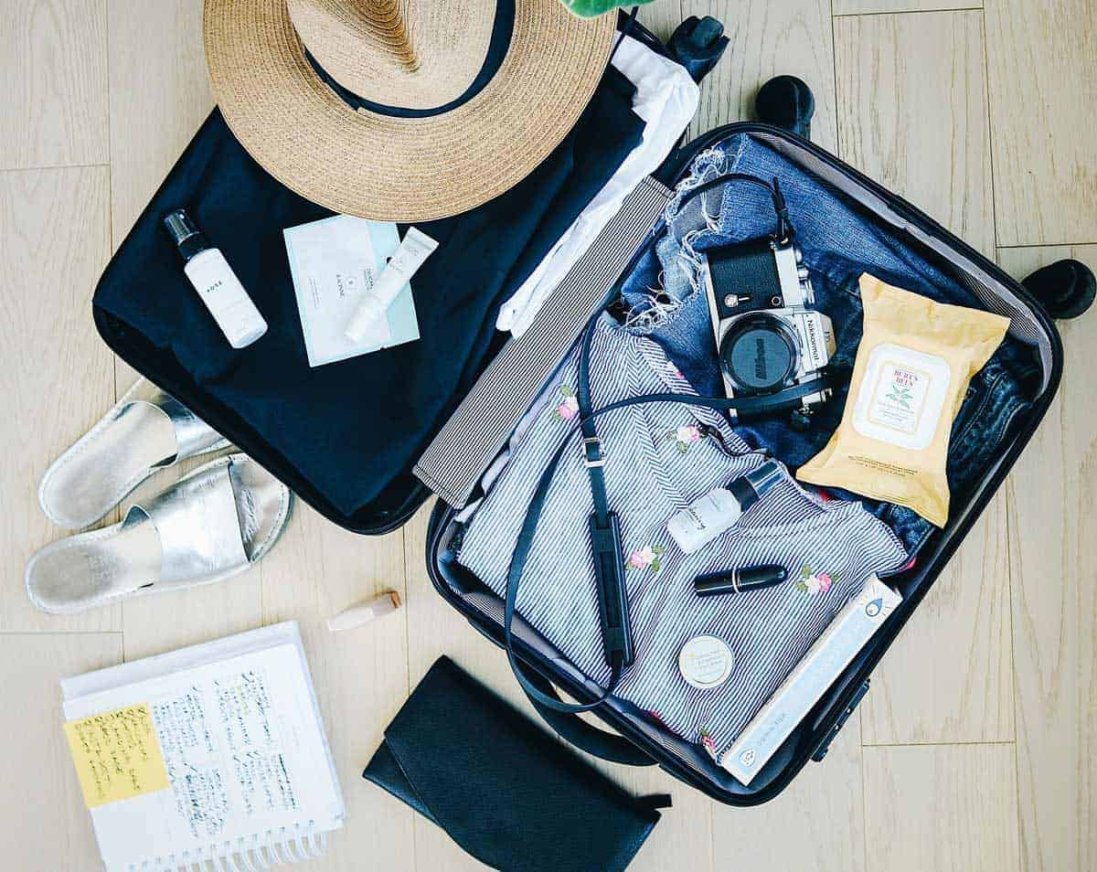 Open suitcase with womens travel gear being packed. Travel safety tips for before you even leave.