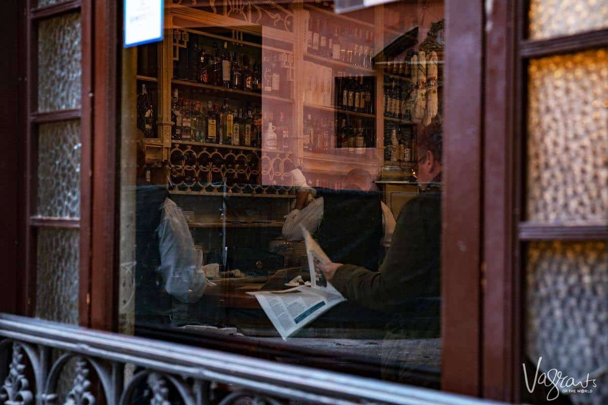 a man reading the paper in El Rinconcillo - the oldest bar in Seville. a more unusual place to find the best food in seville.