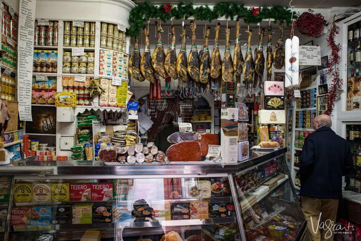 Hanging hams and plenty of cheese and olives at Casa Moreno Sevilles oldest grocery store and secret bar.