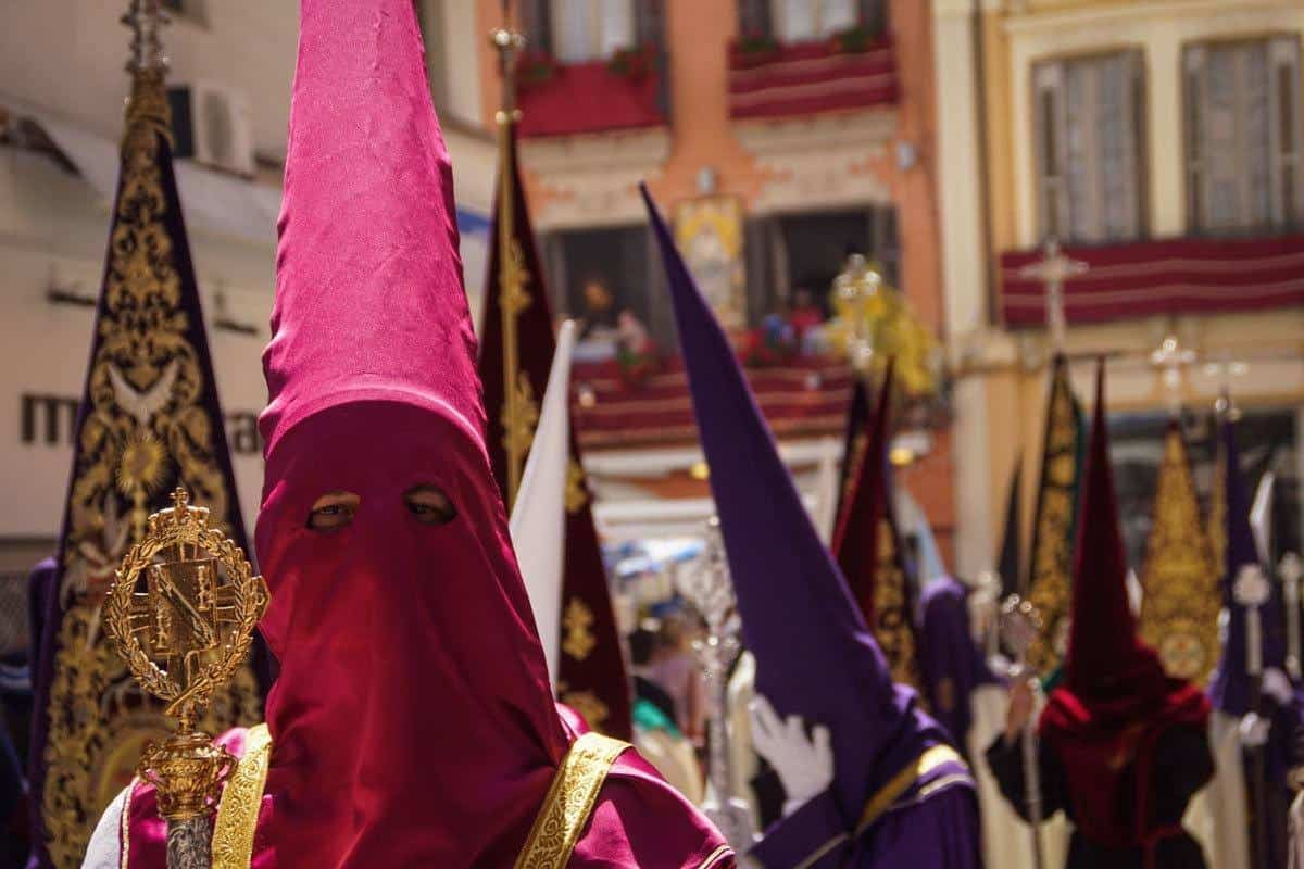 Man wearing pink hood in religious parade during Easter parade in Seville.