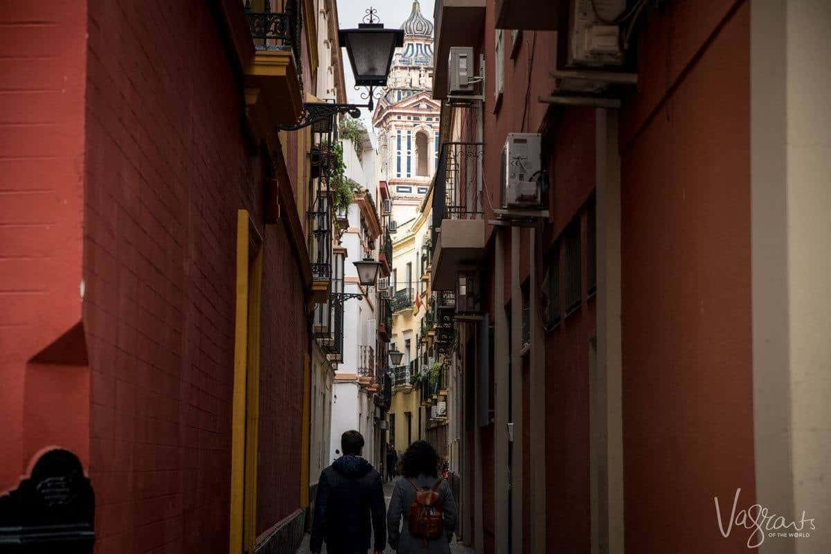 A couple walking down dark narrow streets of Seville.