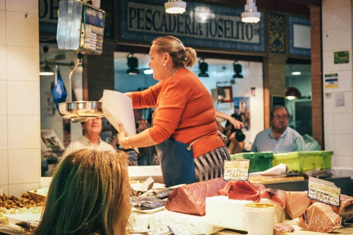 Woman in orange weighing fish at the Triana Market.