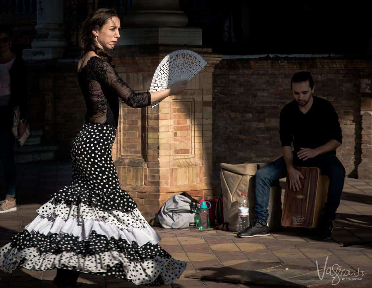 Twirling Flamenco dancer in black and white with a fan dancing on the street in Seville.