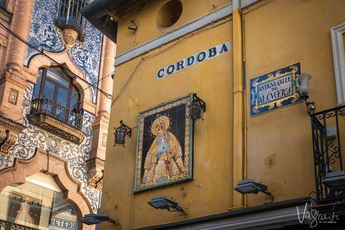 Street corner in Seville CORDOBA with religous tiled artwork on arched buildings. Apart from free things to do in Seville there are some great day trips from Seville