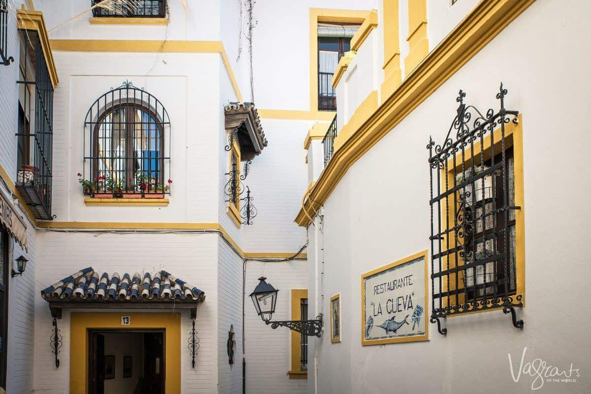 Ornate grated windows, yellow on white walls of houses in Barrio Santa Cruz, don't leave these quant barrios off your Seville itinerary.