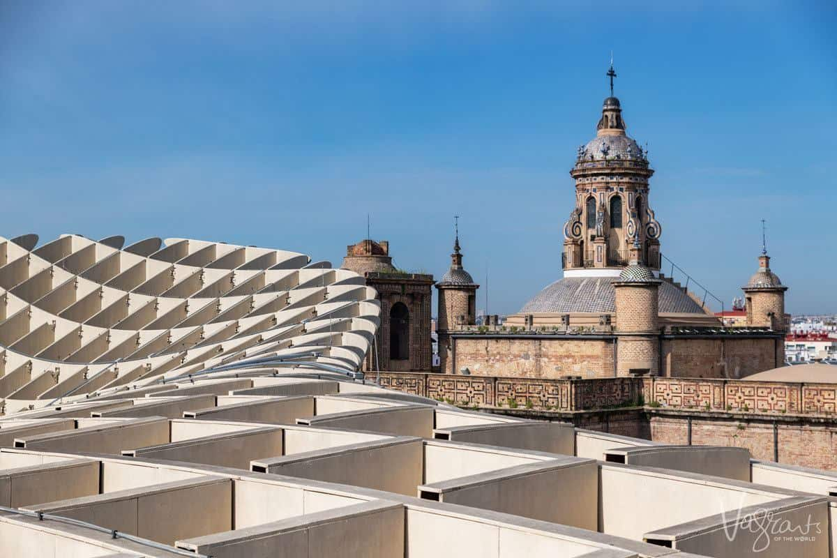 View to the minaret across the catacombed top of Las Setas De Sevilla | The Metropol Parasol. Climbing this structure is an unusual thing to do in seville