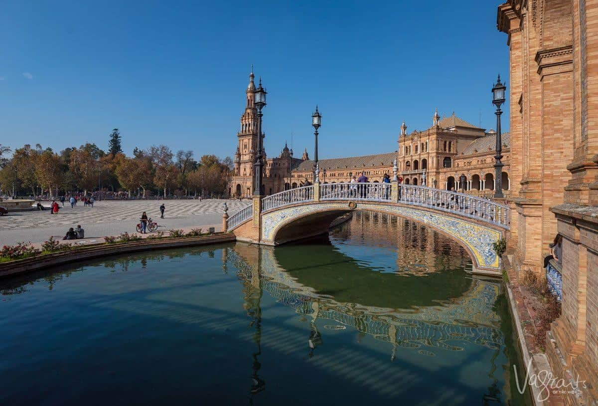 tiled walking bridge over moat around Plaza de España Seville. a horse and carriage is the best way to see seville and they will bring you here to the park