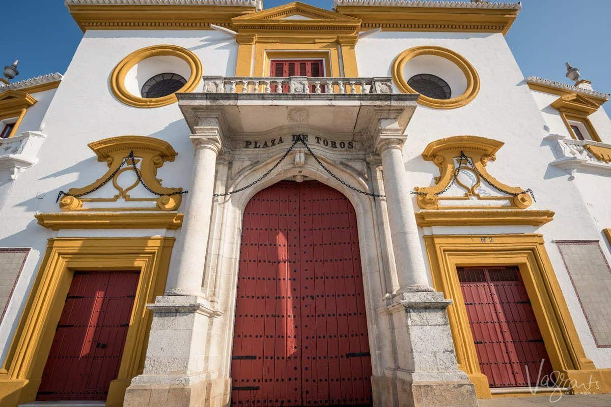 Grand red, white and gold entrance to Plaza de toros de la Real Maestranza de Caballería de Sevilla. If you want to know where to see bullfighting in spain, then this is the place to go for bullfighting in seville.