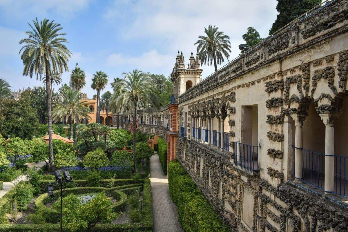 The gardens with palm trees and manicured shrubs next to the wall of Royal Alcazar, One of the most popular attractions in Seville.