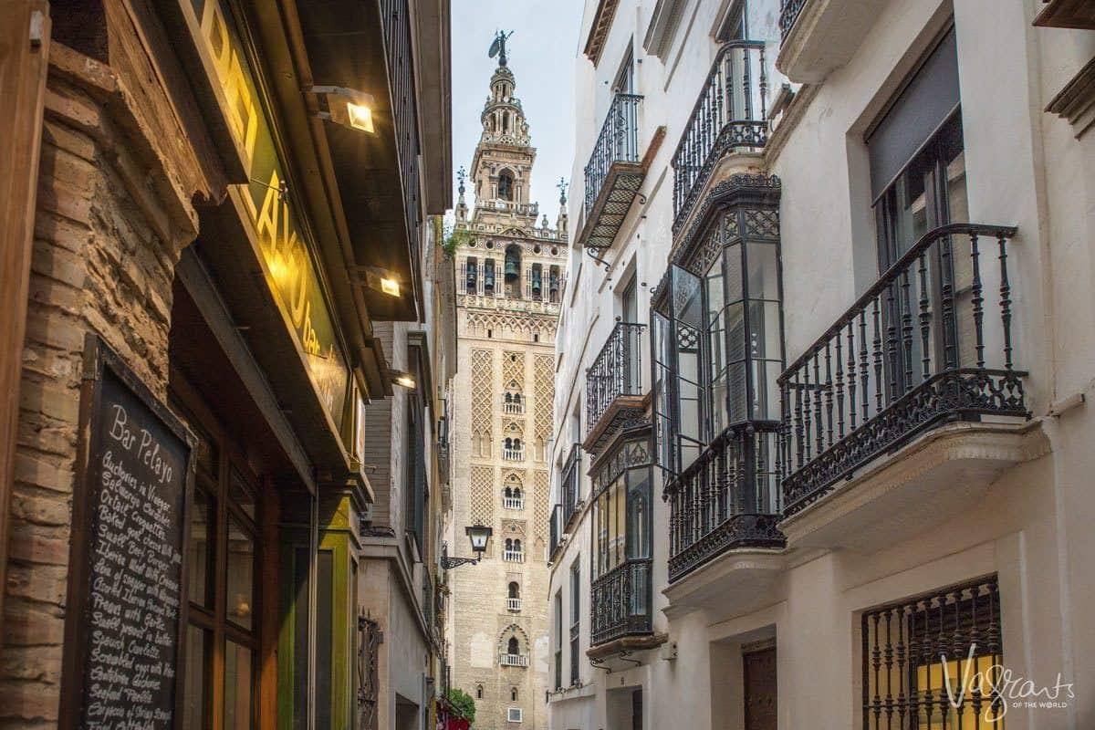 The Giralda Tower viewed from down a narrow street lined with balconies.