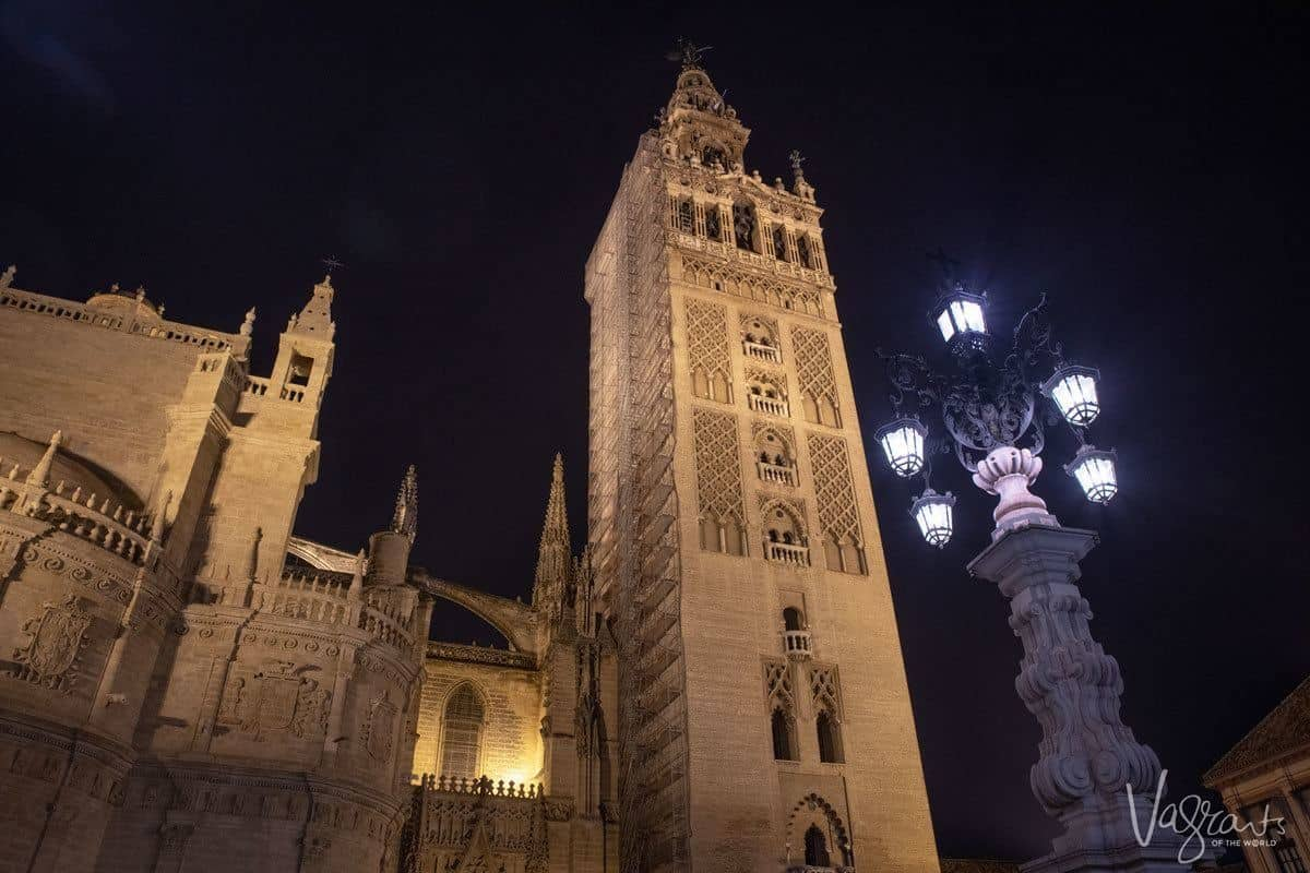 The Giralda Tower and ornate street lamp at night. taking in the night vistas of seville is one of the free things to do in seville