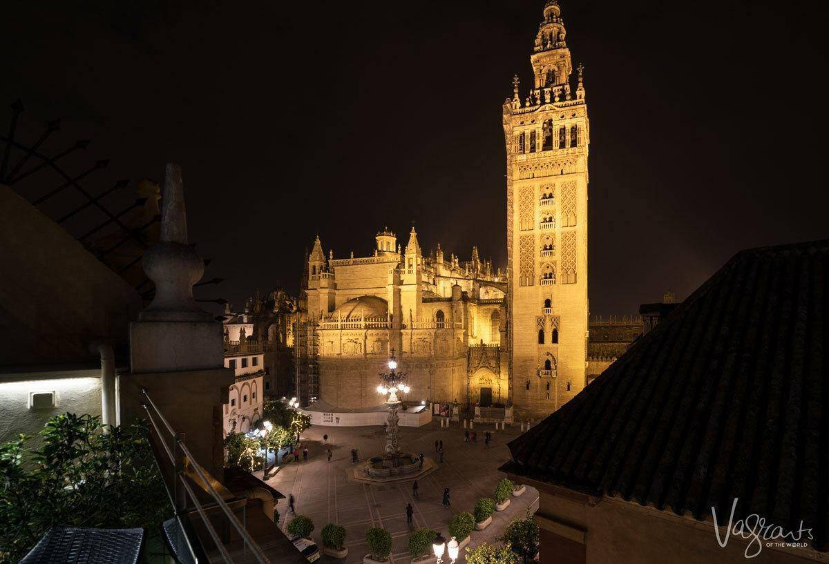 Golden glow of Seville Cathedral lit up at night.