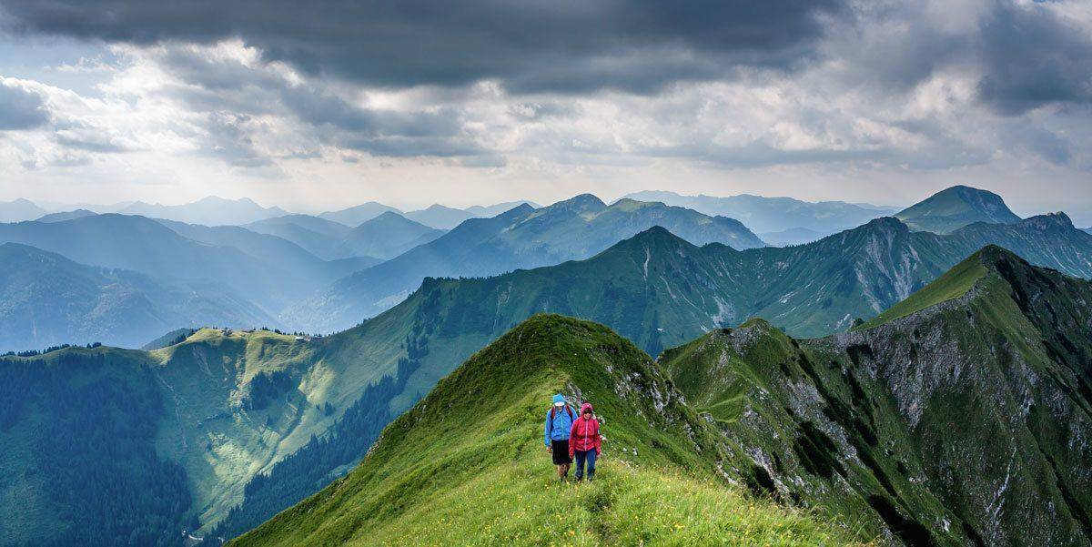 two walkers on a grassy ridge at high altitude.